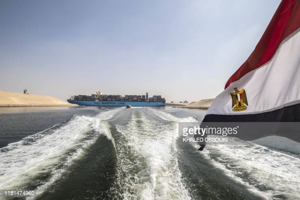 An Egyptian national flag flies on a boat as showsa container ship sails down at the new section of the Suez Canal in the Egyptian port city of...