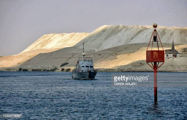 An Egyptian navy craft patrols as ships resume navigation in the Suez Canal on March 30 a day after a cargo vessel was dislodged from its banks. -...