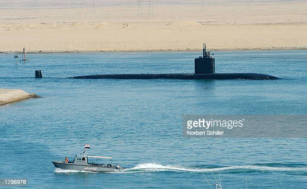 An Egyptian patrolboat tavels past the United States Navy nuclear powered Submarine USS Montpelier as it passes south through the Suez canal towards...