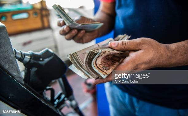 An Egyptian petrol station worker counts cash collected from customers in the capital Cairo on June 29 2017 Egypt announced a new sharp increase in...