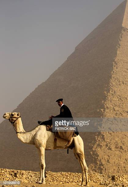 An Egyptian police officer riding a camel stands guard in front of the pyramid of Khafre in Giza on the outskirts of Cairo on November 30 2010 AFP...