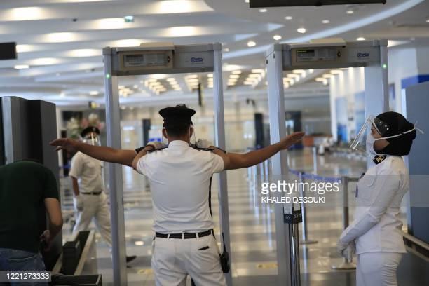 An Egyptian police wearing a protective face shield searches a passenger at the Sharm elSheikh international airport on June 20 2020