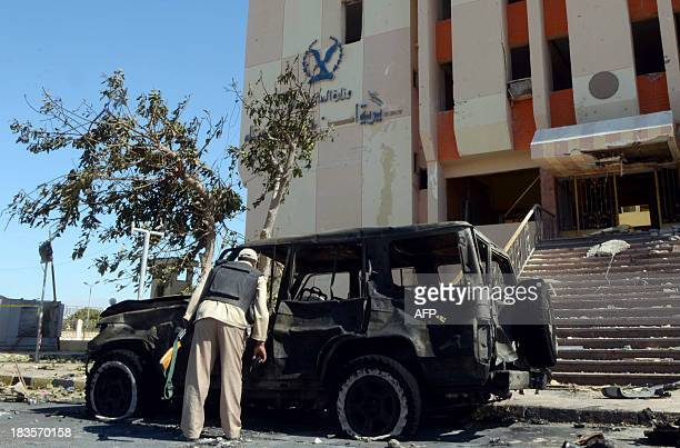 An Egyptian policeman inspects the wreckage of a burnt car at the site of a car bomb explosion which killed three policemen at the Egyptian...