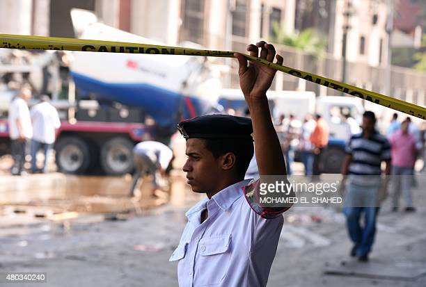 An Egyptian policeman raises a barrier at the site of a powerful bomb explosion that ripped through the Italian consulate killing one person in the...