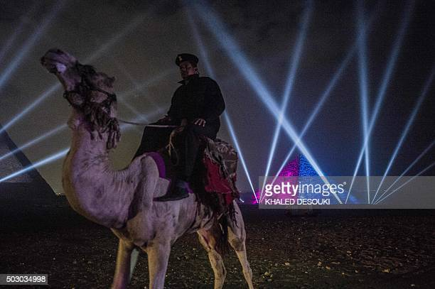 An Egyptian policeman riding a camel stands guard during New Year celebrations in front of the pyramids near the Egyptian capital Cairo on January 1...