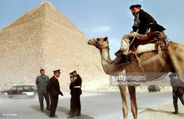 An Egyptian policeman sits on his camel in front of the Cheops Pyramid in Giza 19 November two days after the massacre of 68 people by Islamist...