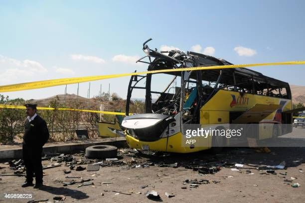 An Egyptian policeman stands guard next to wreckage of a bus that was targeted the day before by a bomb in the Egyptian south Sinai resort town of...