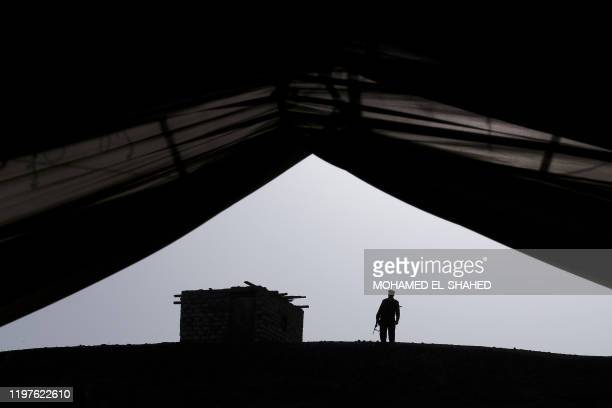 An Egyptian policeman stands guard on the site of the discovery of 3000yearold communal tombs dedicated to high priests in AlGhoreifa in Tuna alJabal...