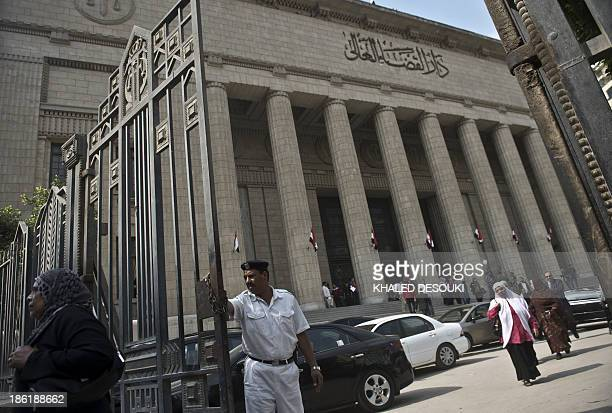 An Egyptian policeman stands guard outside the high court during the second trial hearing of the Muslim Brotherhood chief and aids on October 29 2013...