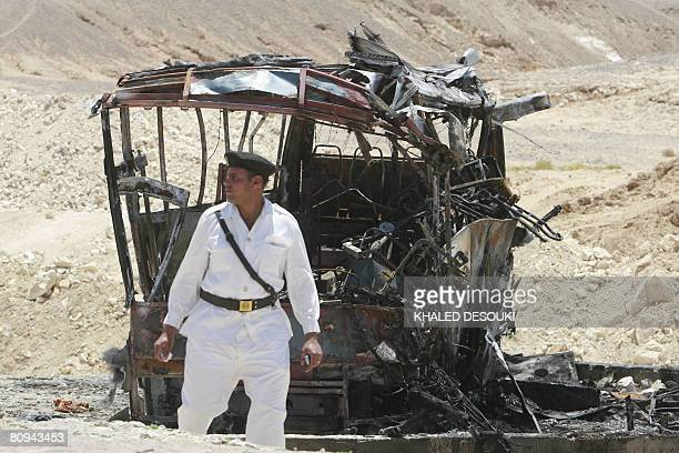 An Egyptian policeman walks in front of the shell of a burned bus which overturned and caught fire killing nine people and injuring 28 in Abu Zinema...