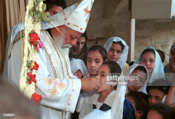 An Egyptian Priest administers Holy Communion during Palm Sunday service April 28 2002 at the Coptic Orthodox Church of Saint Samaan in Cairo Egypt