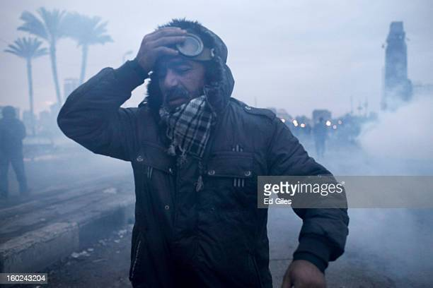 An Egyptian protester affected by exposure to tear gas walks away from clashes between protesters and Egyptian riot police near Tahrir Square on...