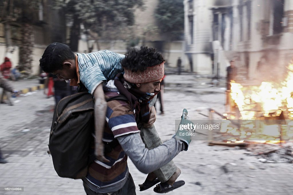 An Egyptian protester carries an injured boy away from clashes with Egyptian riot police during a protest following the announcement of the death penalty for 21 suspects in connection with a football stadium massacre last year, on January 26, in Cairo, Egypt. Protests have continued across Egypt after a verdict was announced in a case over the deaths of more than seventy fans of Egypt's Al-Ahly football club in a stadium massacre on February 1, 2012, in the northern city of Port Said, during a brawl that began minutes after the final whistle of a match between Al-Ahly and opposing side, Al-Masry. 21 fans of the opposing side, Al-Masry, were given the death penalty in the court case, a verdict that must now be approved by Egypt's Grand Mufti. The verdict was handed down during a period of high tension across Egypt, one day after the second anniversary of the beginning of Egypt's 2011 revolution that overthrew former President, Hosni Mubarak.