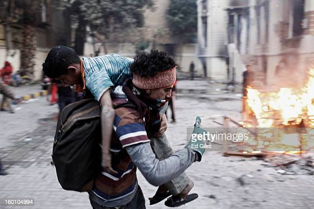 An Egyptian protester carries an injured boy away from clashes with Egyptian riot police during a protest following the announcement of the death...