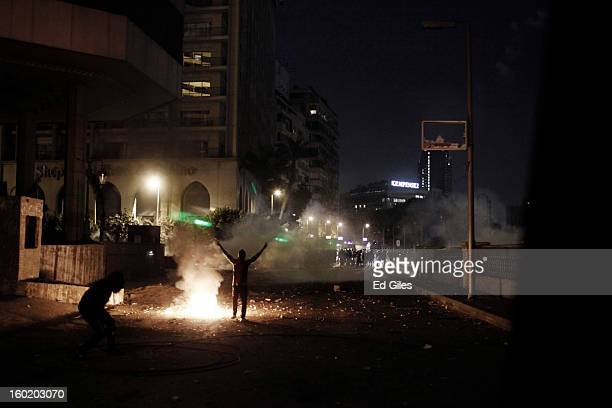 An Egyptian protester gestures toward a line of riot police during clashes with Egyptian security forces near Tahrir Square on January 27 2013 in...