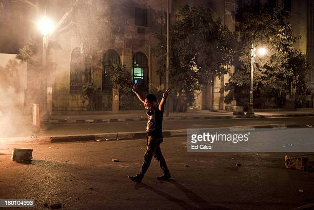 An Egyptian protester gestures toward Egyptian riot police during a protest following the announcement of the death penalty for 21 suspects in...