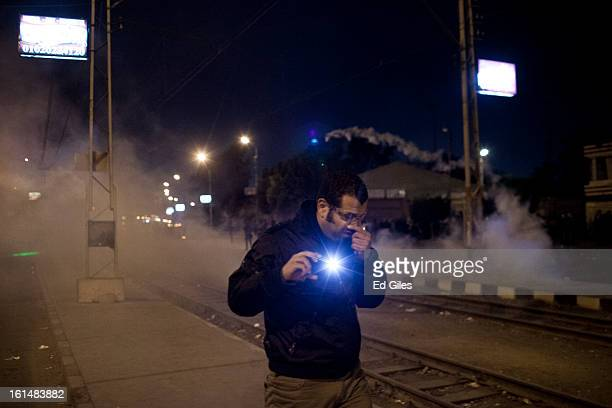 An Egyptian protester holding a mobile phone walks away from tear gas fired by nearby Egyptian riot police during violent protests by the...