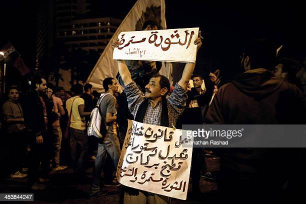 An Egyptian protester holds a banner that reads 'the revolution continues' during a march to the Shura Council, Cairo, Egypt in objection to the new...