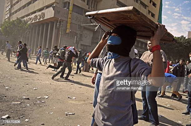 An Egyptian protester holds a hand-made shield to avoid rocks during clashes with riot police in Tahrir Square on January 25, 2013 on the second...