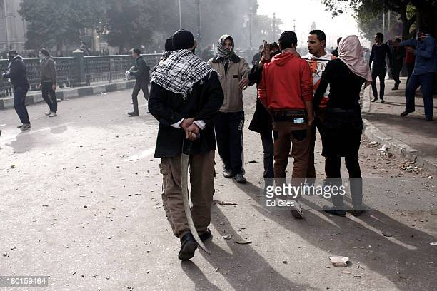 An Egyptian protester holds a homemade sword behind his back during a demonstration in Tahrir Square on January 27 2013 in Cairo Egypt Violent...