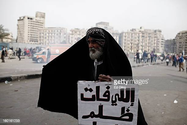 An Egyptian protester holds a sign while standing in a cloud of tear gas fired by riot police during a demonstration in Tahrir Square on January 27...