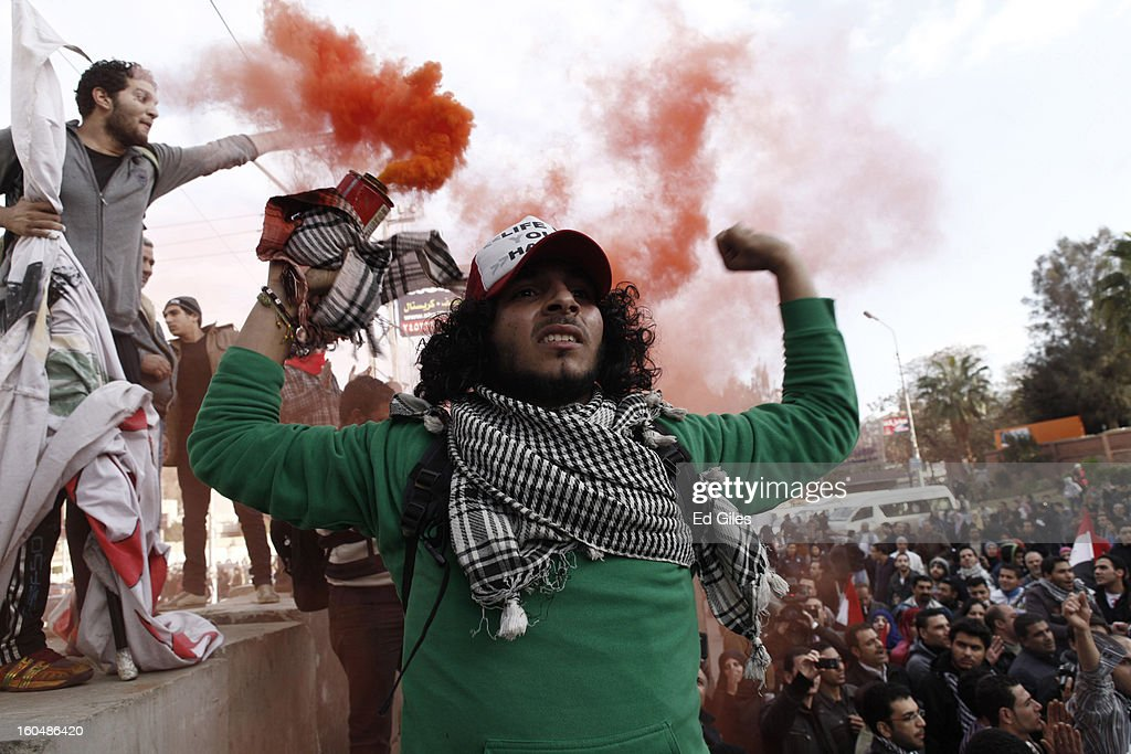 An Egyptian protester holds a smoke flare during anti-government protests outside the Egyptian Presidential Palace in the suburb of Heliopolis on February 1, 2013 in Cairo, Egypt. Protests continued across Egypt nearly one week after the second anniversary of the Egyptian Revolution that overthrew former President Hosni Mubarak on January 25, 2011. Further protests are expected over the weekend to commemorate the first anniversary of the Port Said football massace, when over 70 fans of the Cairo-based Al Ahly football club were killed in a violent post-match brawl between fans of the opposing teams inside the Port Said football stadium after a match between the Al Ahly and Al Masry football teams. (Photo by Ed Giles/Getty Images).