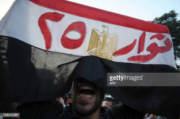 An Egyptian protester holds his national flag bearing the slogan 'Revolutionaries of the 25th' refering to the revolution of January 25 that toppled...
