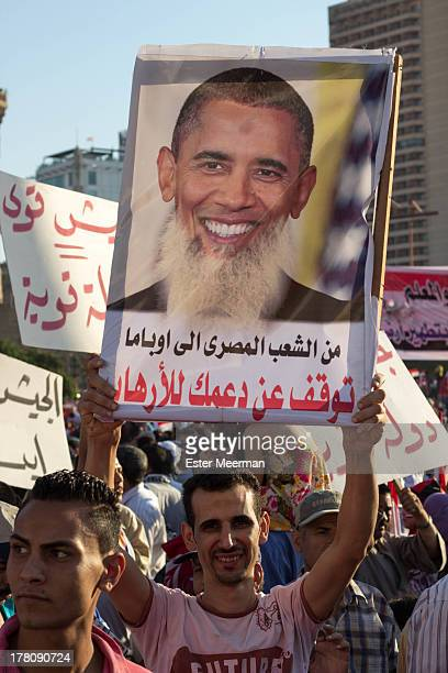 An Egyptian protester holds up a sign against the American president Barack Obama on Tahrir square on the 26th of July 2013, the day army general...
