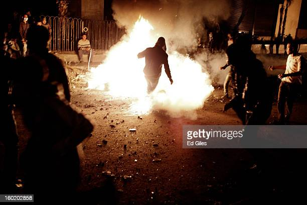 An Egyptian protester kicks a live tear gas canister into a fire during clashes with riot police near Tahrir Square on January 27 2013 in Cairo Egypt...