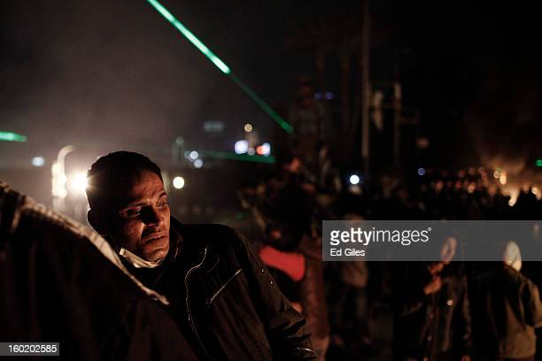 An Egyptian protester looks toward a nearby fire lit during clashes with riot police near Tahrir Square on January 27 2013 in Cairo Egypt Violent...