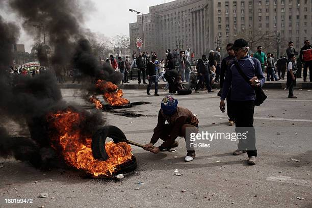 An Egyptian protester places a tire on a fire during a demonstration in Tahrir Square on January 27 2013 in Cairo Egypt Violent protests continued...