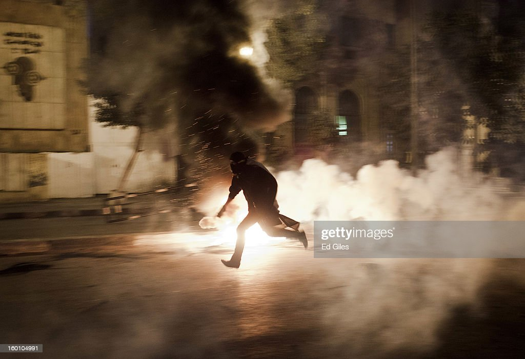 An Egyptian protester runs with a live tear gas canister toward Egyptian riot police during a protest following the announcement of the death penalty for 21 suspects in connection with a football stadium massacre last year, on January 26, in Cairo, Egypt. Protests have continued across Egypt after a verdict was announced in a case over the deaths of more than seventy fans of Egypt's Al-Ahly football club in a stadium massacre on February 1, 2012, in the northern city of Port Said, during a brawl that began minutes after the final whistle of a match between Al-Ahly and opposing side, Al-Masry. 21 fans of the opposing side, Al-Masry, were given the death penalty in the court case, a verdict that must now be approved by Egypt's Grand Mufti. The verdict was handed down during a period of high tension across Egypt, one day after the second anniversary of the beginning of Egypt's 2011 revolution that overthrew former President, Hosni Mubarak.