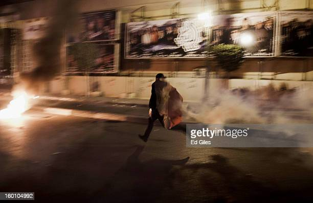 An Egyptian protester runs with a live tear gas canister toward Egyptian riot police during a protest following the announcement of the death penalty...