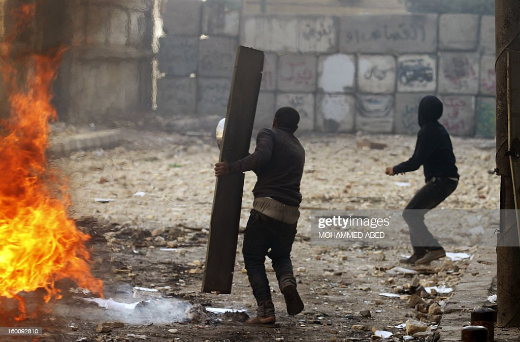 An Egyptian protester shields himself using a piece of metal as they throw stones towards riot police during a demonstration in Cairo's Tahrir Square on January 26, 2013. Egypt's Islamist President Mohamed Morsi appealed for calm after at least seven people were killed in violence on the second anniversary of the revolution that ousted Hosni Mubarak.