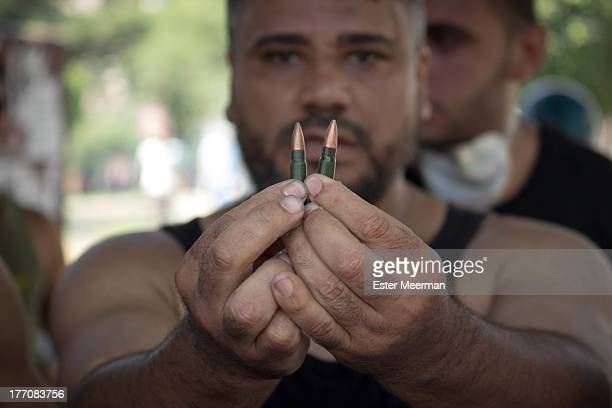 CONTENT] An Egyptian protester showing live ammunition that was supposedly used by riot police bullets shown are unused