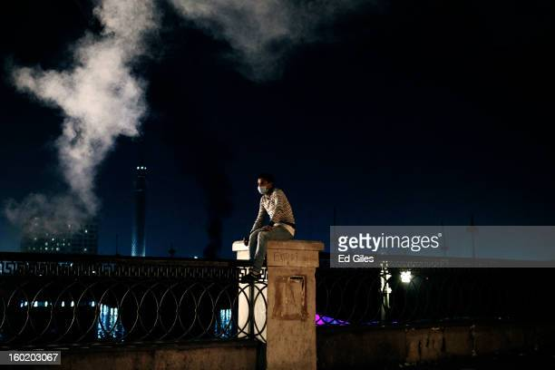 An Egyptian protester sits on a fence underneath a cloud of tear gas during clashes with riot police near Tahrir Square on January 27 2013 in Cairo...