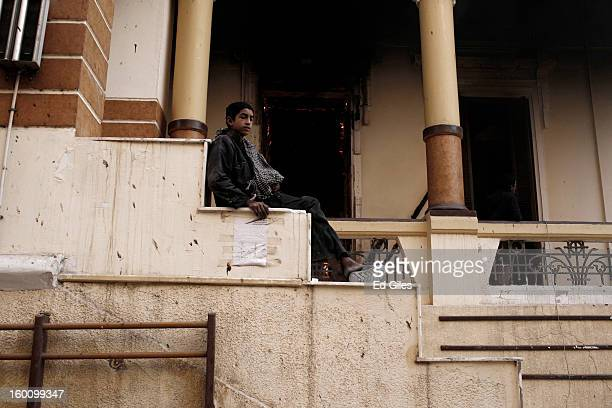 An Egyptian protester sits on the steps of a burning school building during a demonstration following the announcement of the death penalty for 21...