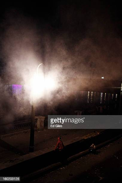 An Egyptian protester sits underneath a street lamp shrouded in tear gas during clashes with riot police near Tahrir Square on January 27 2013 in...