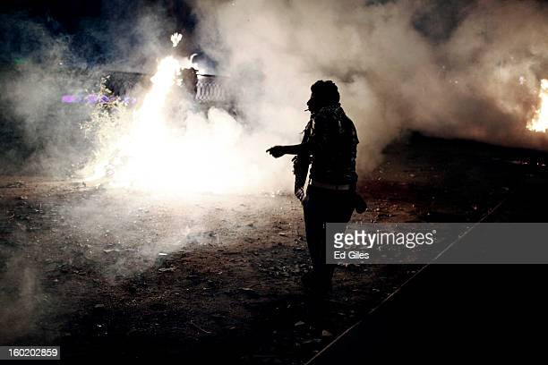 An Egyptian protester stands amongst smoke and tear gas during clashes with riot police near Tahrir Square on January 27 2013 in Cairo Egypt Violent...