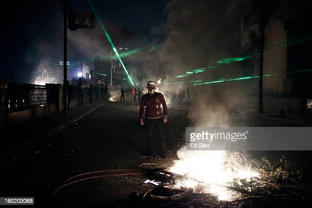 An Egyptian protester stands by a fire lit during clashes with riot police near Tahrir Square on January 27 2013 in Cairo Egypt Violent protests...