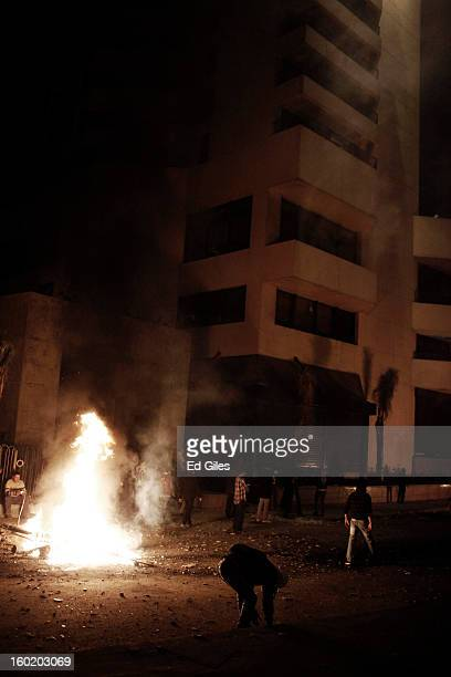An Egyptian protester stands by a fire lit during clashes with riot police outside the luxury Intercontinental hotel near Tahrir Square on January 27...