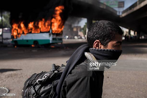 An Egyptian protester stands in front of a burning bus set alight during violent clashes between supporters of Egyptian President Mohammed Morsi and...