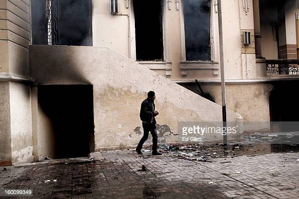 An Egyptian protester stands in front of a burning school building during a demonstration following the announcement of the death penalty for 21...
