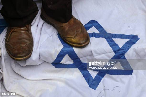 TOPSHOT An Egyptian protester steps on an Israeli flag during a demonstration against the US president's recognition of Jerusalem as Israel's capital...