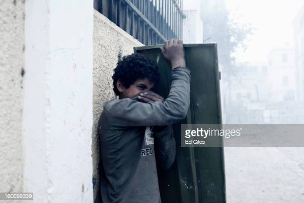 An Egyptian protester suffers from exposure to tear gas fired by Egyptian riot police during a protest following the announcement of the death...