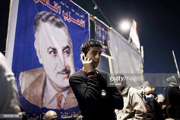 An Egyptian protester talks on a mobile phone standing below a poster of former secular Egyptian President Gamal Abdel Nasser during a demonstration...