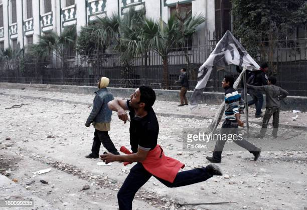 An Egyptian protester throws a rock toward Egyptian riot police during a protest following the announcement of the death penalty for 21 suspects in...