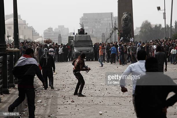 An Egyptian protester throws a rock towards riot police during a demonstration in Tahrir Square on January 27 2013 in Cairo Egypt Violent protests...