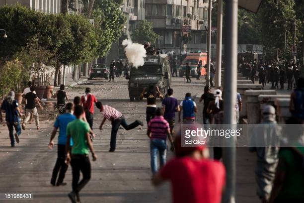 An Egyptian protester throws an improvised explosive toward an approaching riot police van during clashes near the United States Embassy on the Nile...