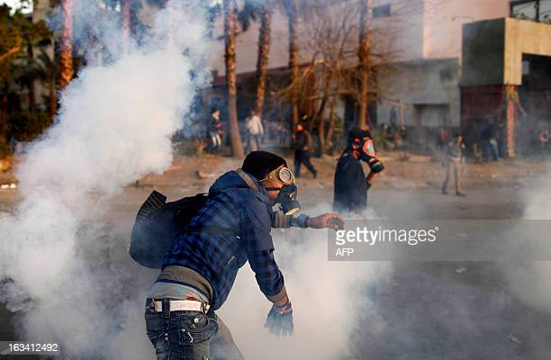 An Egyptian protester throws back tear gas canisters during clashes with riot police near Tahrir Square in Cairo on March 9, 2013. A court verdict...